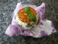 hotový labneh v kelímku s ubrouskem a ozdobený ještě plátkem sušeného rajčete a čerstvou bazalkou
